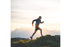 A man runs on a mountain top as part of his men's health routine for fitness.