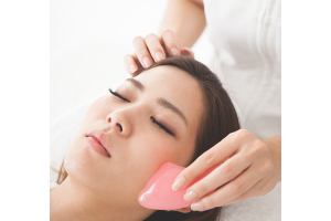 A woman uses the Gua Sha practice to reduce inflammation as part of her skincare routine.