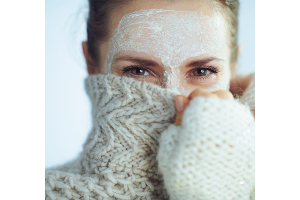 A woman protects her skin by enhancing her winter skincare routine.