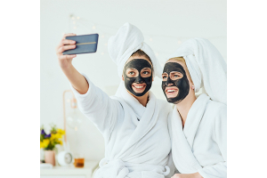 Friends enjoy beauty masks together at home as part of their skincare routine.