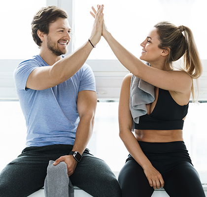A couple at the gym practicing healthy skincare and hair care.