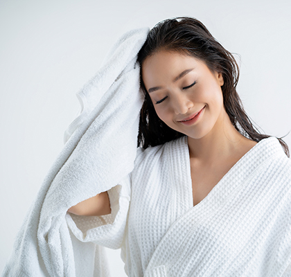 A woman dries her hair as part of her expert at-home hair care routine.