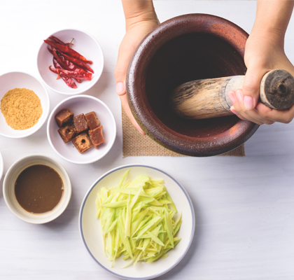 A person mixes herbal remedies in a mortar and pestle.