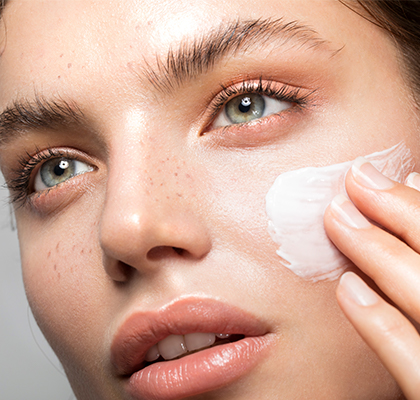 A woman applies her beauty mask as part of her skincare routine.